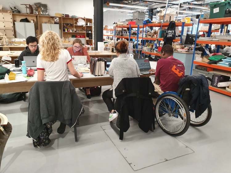 Image of students working around a table at a workshop space at UCL