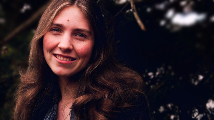Image of Kirsten outside against a tree, smiling at the camera