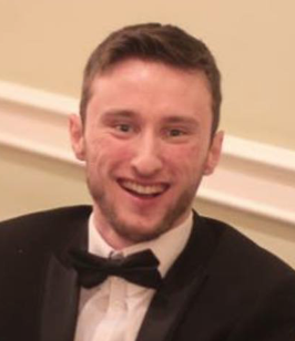 Image of Matt looking and smiling at the camera, dressed in a tuxedo