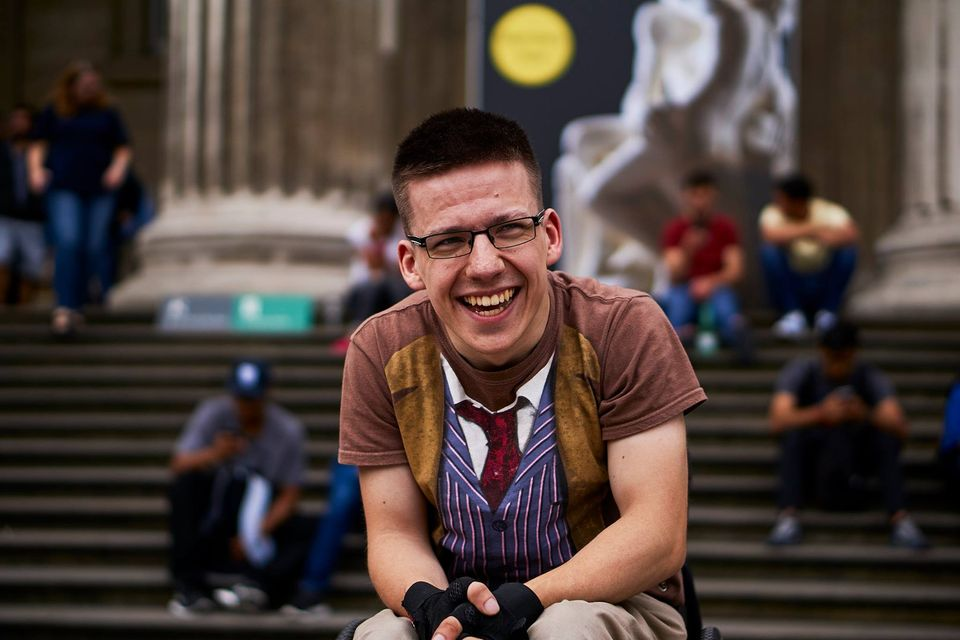 Image of Kyle, outside of a university building, smiling at the camera