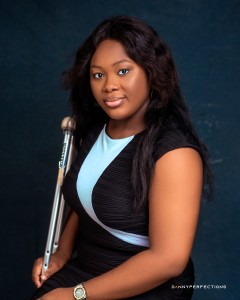 Uzoamaka is sat down and smiling to the camera, wearing a black dress and holding her crutch