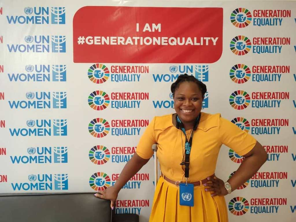 Uzoamaka looks towards the camera smiling in a yellow dress with her hand rested on her hip, she has a crutch positioned under her right arm. Uzoamaka stands in front of a UN women sign that has a slogan I am #GenerationEquality